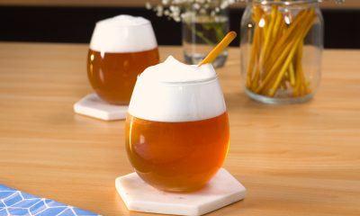 Dua gelas cheese tea disajikan di atas meja kayu.