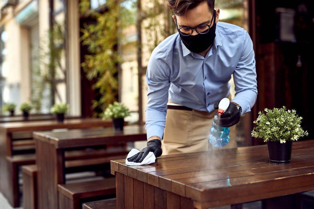 Pramusaji mengelap meja restoran sambil memakai masker