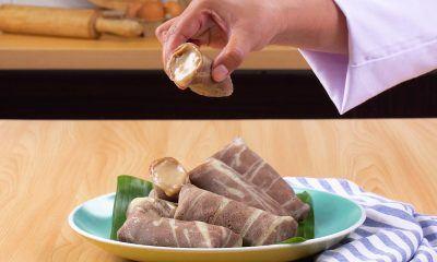 Seorang chef tengah menikmati kue dadar gulung hasil buatannya sendiri di dapur.