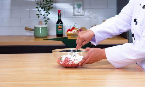 Seorang chef mengaduk daging kambing cincang dengan bumbu.