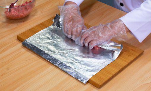Seorang chef tengah menggulung daging kambing dengan aluminium foil.
