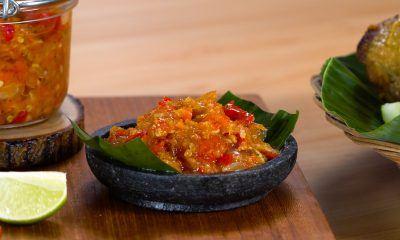 Sambal bawang disajikan dalam cobek di atas talenan.