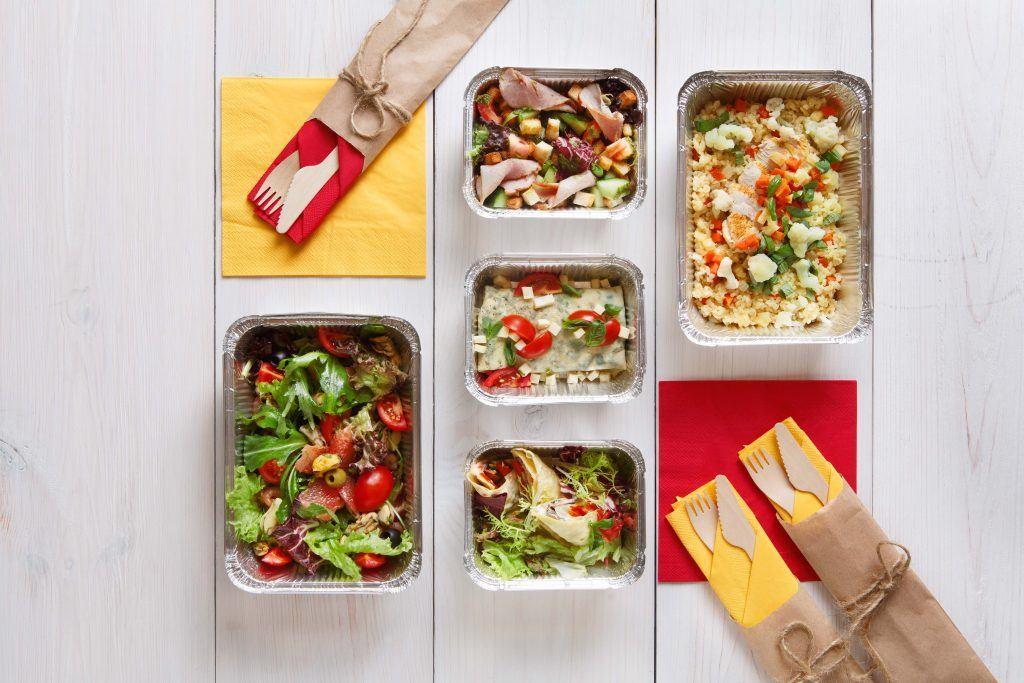 Empat kotak jajan sehat berisi makanan sehat dan sendok garpu kayu
