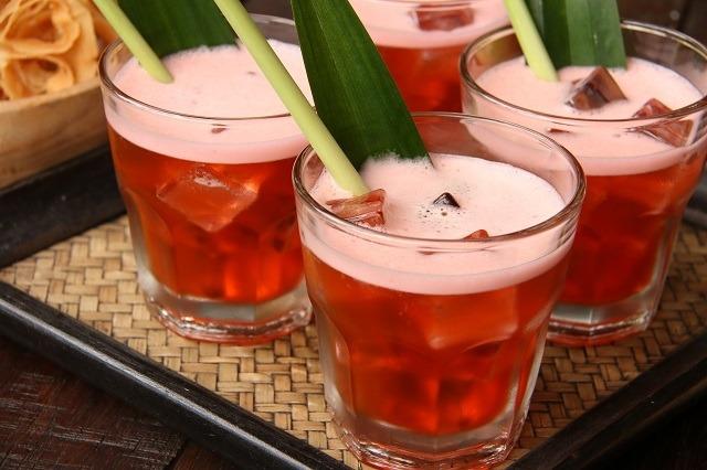 Es teh mawar disajikan di atas baki dengan daun pandan dan serai.