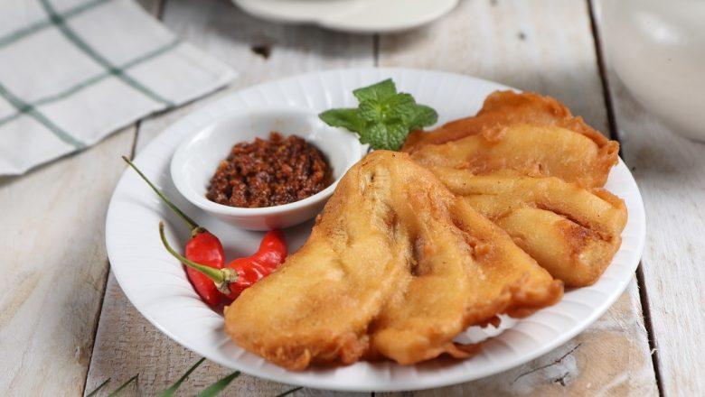Pisang goreng sambal roa disajikan di atas piring yang diletakkan di atas meja kayu aneka gorengan.