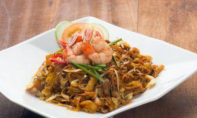 Sepiring kwetiau goreng seafood lengkap dengan topping udang dan garnish.
