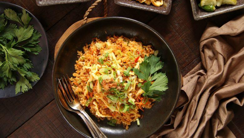 Nasi goreng padang di piring dikeliling piring kecil berisi sambal dan telur.