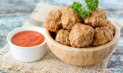 Hasil masak resep bakso goreng disajikan dalam mangkuk kayu dan didampingi saus sambal.