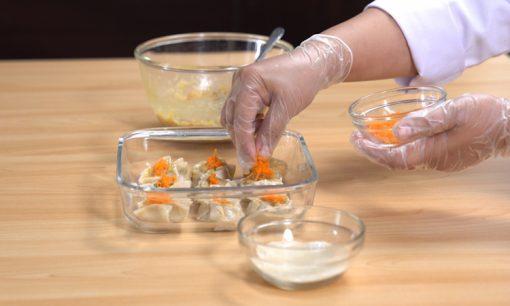 Mengisi lembaran kulit pangsit dengan adonan ayam udang untuk resep dimsum ayam.