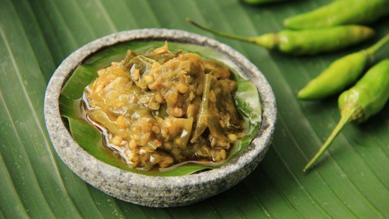 Sambal ijo disajikan dalam cobek mini dan didampingi cabai rawit serta diletakkan di atas daun pisang.