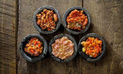 Aneka sambal diletakkan dalam cobek mini di atas meja kayu.