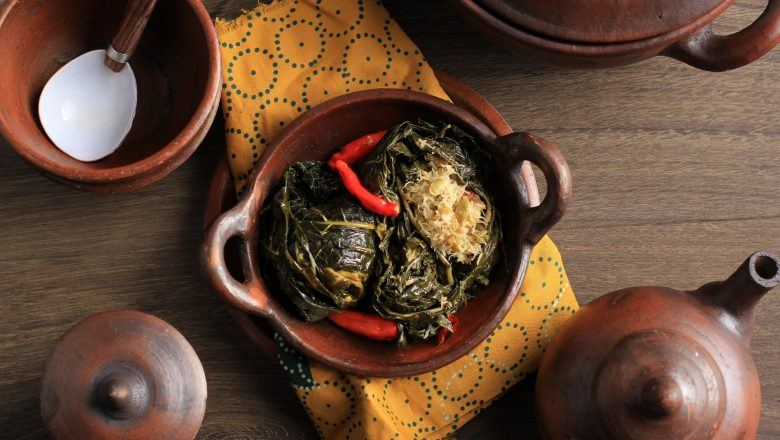 Buntil daun singkong dalam piring tanah liat dengan napkin batik