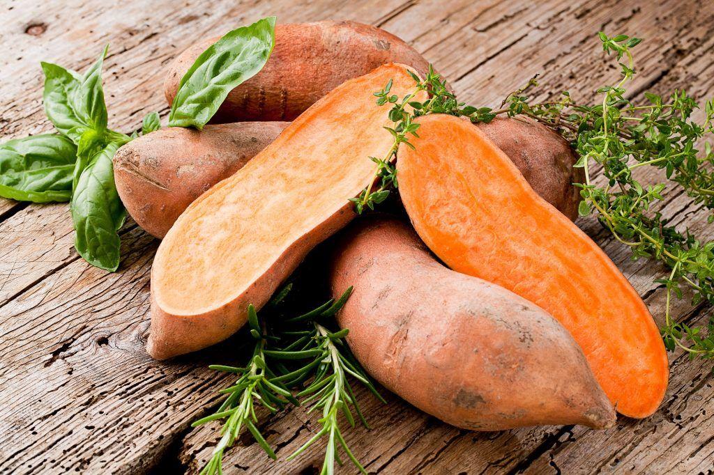 Beberapa ubi jalar oranye di atas papan kayu