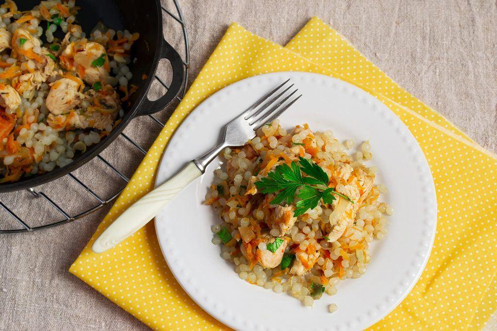 Piring putih berisi karbohidrat jenis nasi barley goreng.