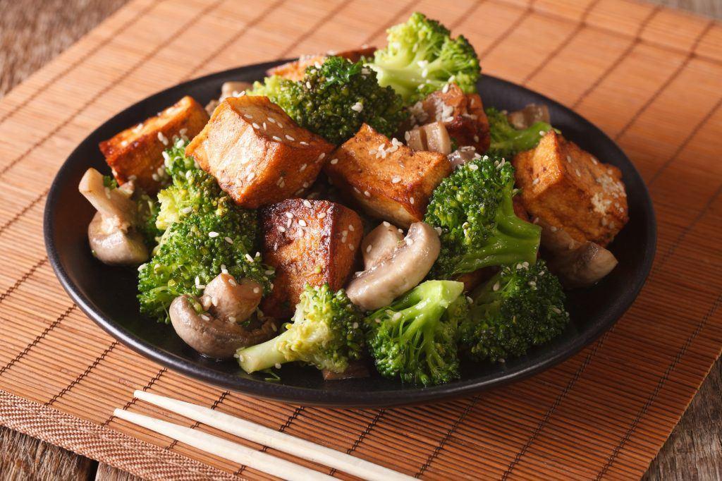 Tumis brokoli tahu jamur di atas piring hitam sebagai menu vegetarian enak