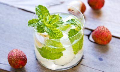 Segelas mocktail lychee dengan daun mint dikelilingi buah leci import