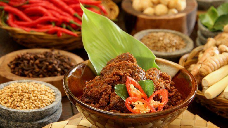 Rendang crispy dalam mangkuk bambu dan rempah di belakangnya