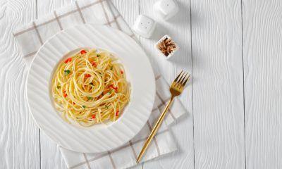 Resep aglio olio disajikan dalam piring putih di atas serbet dan meja kayu putih.