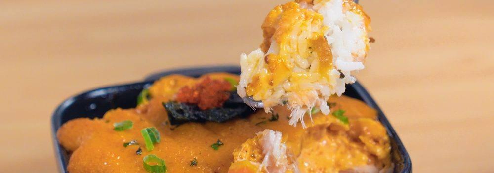 Salmon mentai hangat tengah dinikmati dengan menggunakan sendok.
