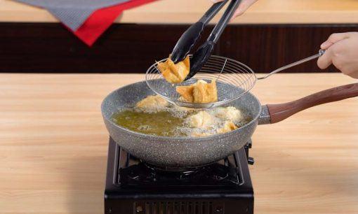 Menggoreng batagor menggunakan minyak panas.
