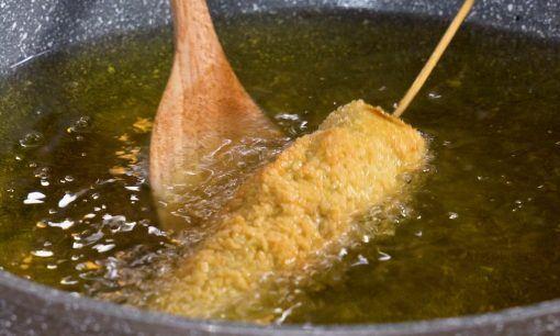 Menggoreng corn dog dalam minyak panas.