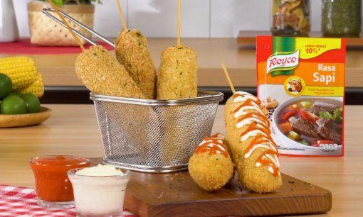 Corn dog disajikan di atas talenan dengan saus.
