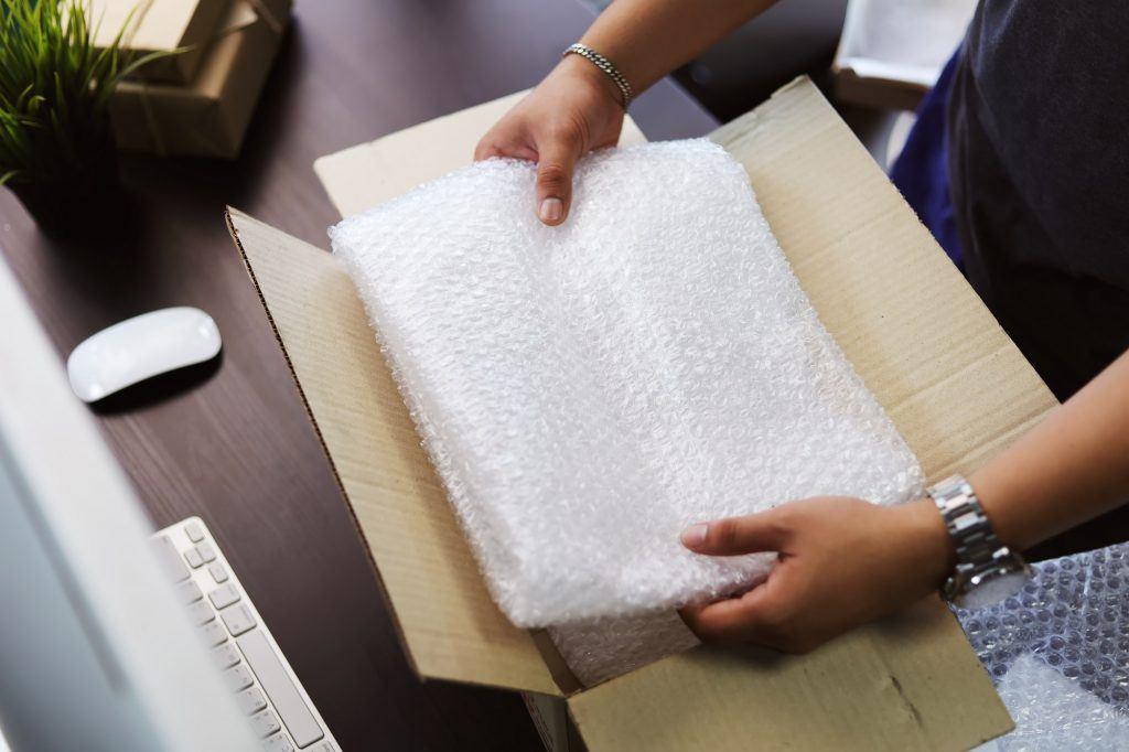 Seorang pria melapisi paket dengan bubble wrap