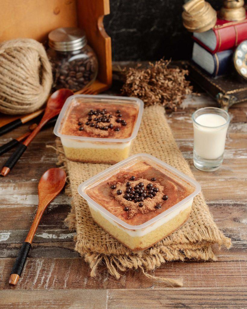Dua dessert box tiramisu dengan susu dan sendok kayu di sampingnya.