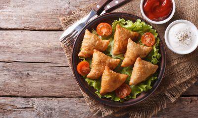 Samosa disajikan dalam piring hitam dan disandingkan dengan saus sambal.