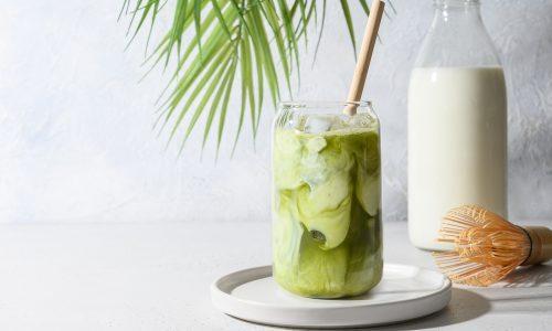 Green tea dengan susu almond disajikan dalam gelas panjang.