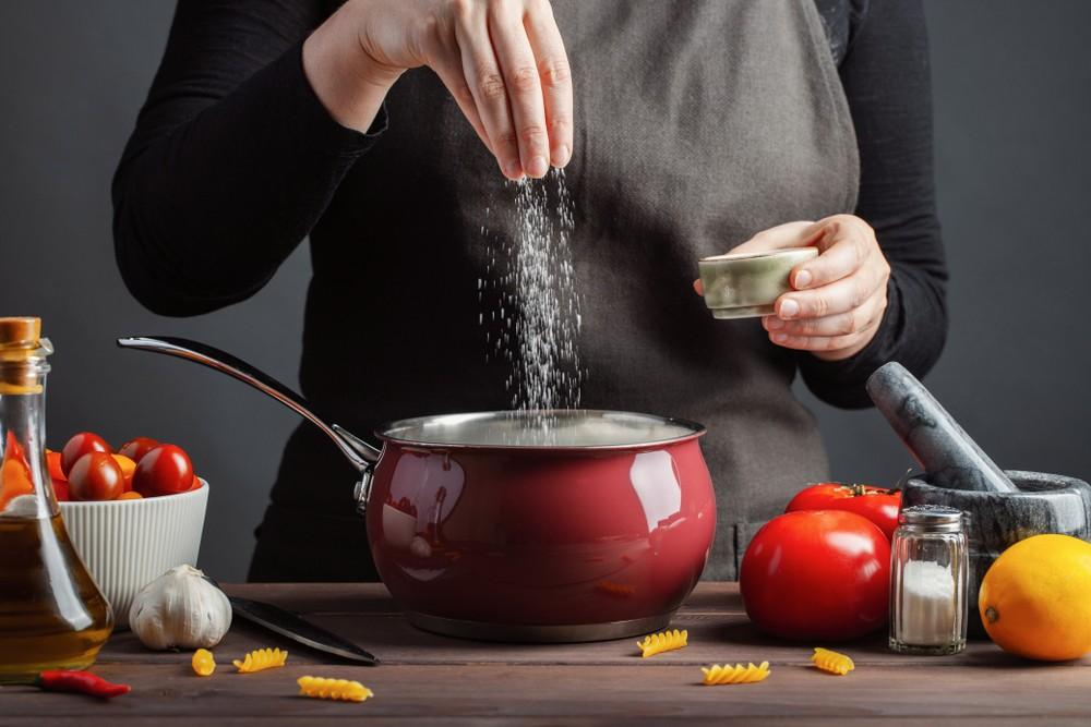Seorang wanita tengah membubuhkan garam pada masakannya.
