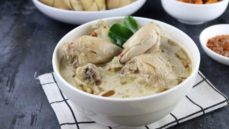 Semangkuk opor ayam putih disajikan bersama ketupat dan kawan-kawan.