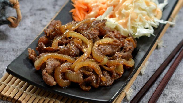 Sepiring hasil masak resep beef teriyaki disajikan dengan salad, nasi, dan sup.