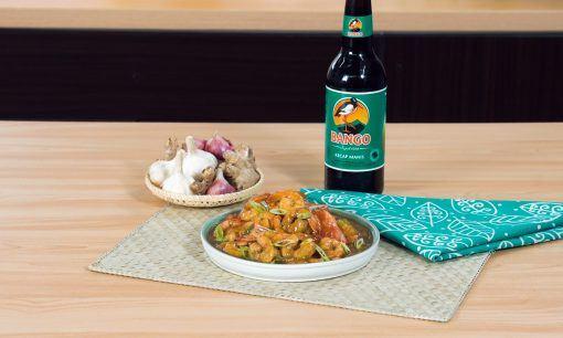 Tumis udang kecap disajikan di atas meja makan bersama kecap manis.