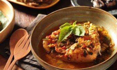 Semangkuk ikan woku belanga dialasi kain di meja saji