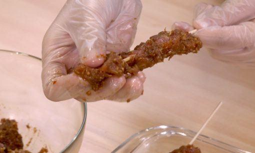 Menusukkan daging dengan tusukan sate.
