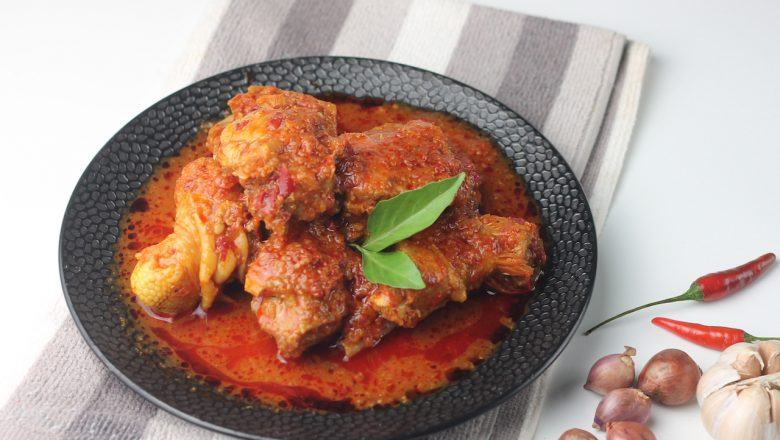 Hasil dari resep ayam bumbu bali pedas di piring hitam di atas serbet