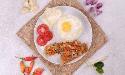 Ikan goreng tepung sambal matah dengan nasi dan telur di piring putih.