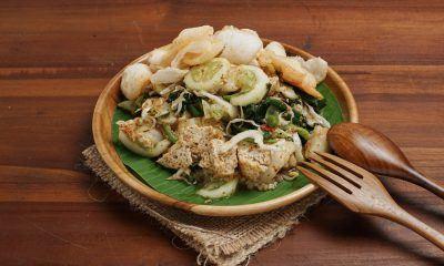 Hasil masak resep lotek Bandung beralas daun pisang hijau di piring cokelat dan sendok garpu.