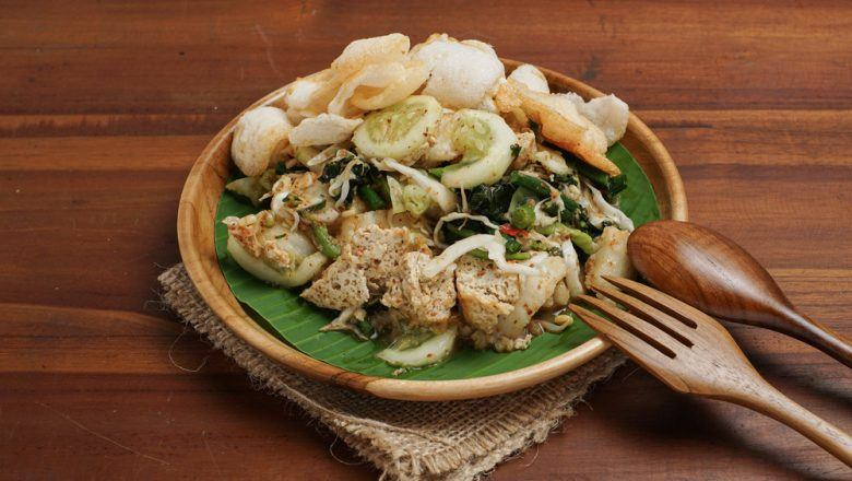 Lotek Bandung beralas daun pisang hijau di piring cokelat dan sendok garpu.