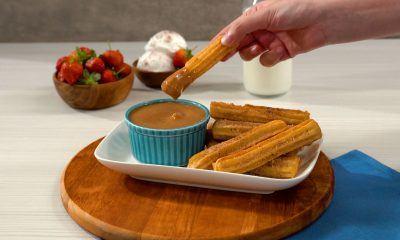 Seseorang tengah mengambil hasil cara membuat churros di atas meja.