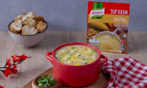 Sup asparagus jagung disajikan dalam mangkuk merah bersama produk dan bumbu.