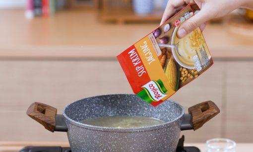Menuangkan sebungkus Royco Sup Krim Jagung ke dalam panci.