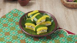 Resep lemper ayam kuning di atas daun pisang di piring cokelat