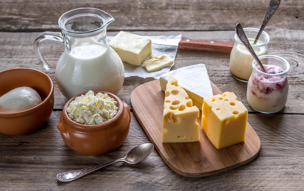 Susu dan keju disajikan di atas meja kayu.
