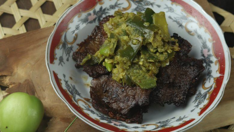 Hasil masak resep hati sapi dipadukan dengan balado hijau disajikan di atas meja kayu.