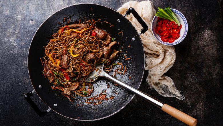 Hasil masak resep mie telur sapi lada hitam selesai dimasak di atas wok hitam.