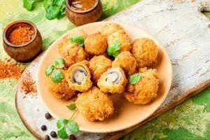 Sepiring jamur kancing crispy goreng disajikan hangat.