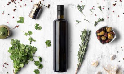 Botol berisi minyak zaitun dikelilingi bahan masakan.
