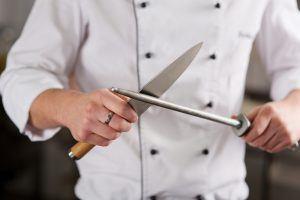 seorang chef tengah menajamkan pisau